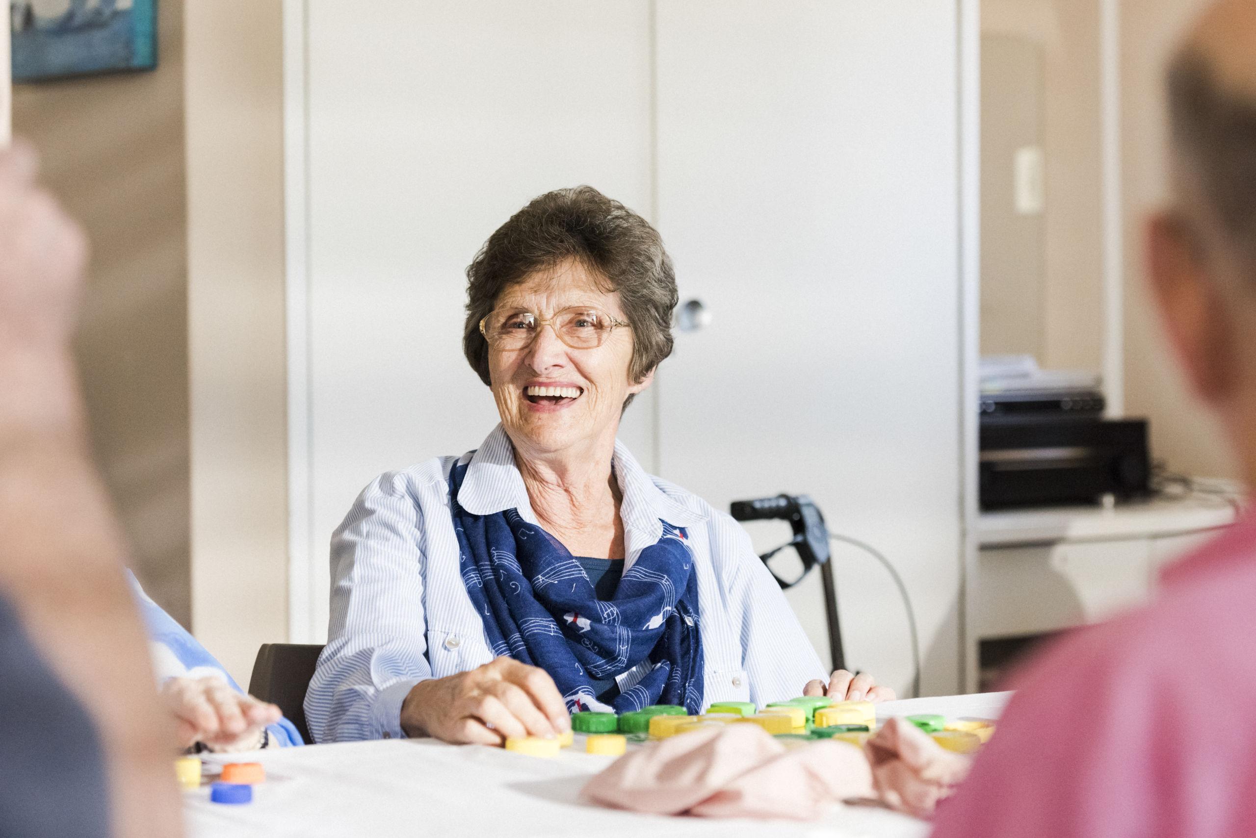 Oudere vrouw met dementie lacht tijdens een leuke activiteit bij Hesti a Zorgs