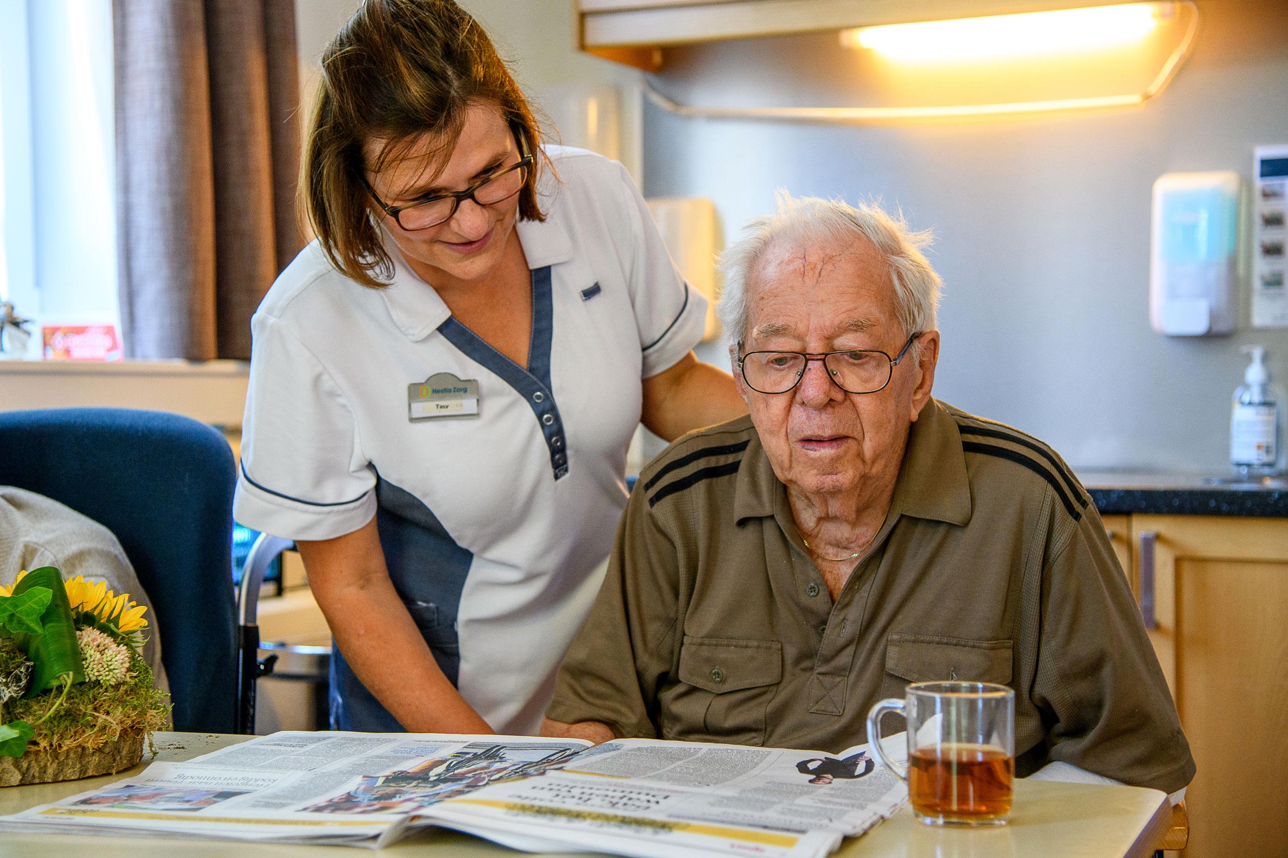 Begeleider ondersteunt dementerende ouder met het doornemen van de krant