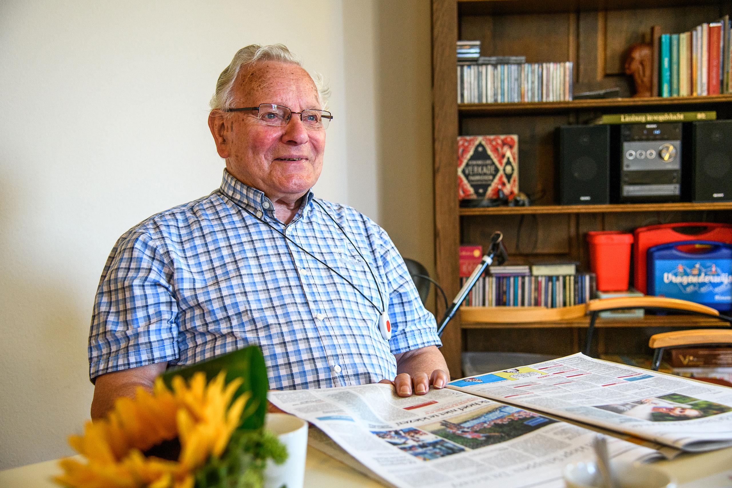 Oudere man leest de krant aan tafel
